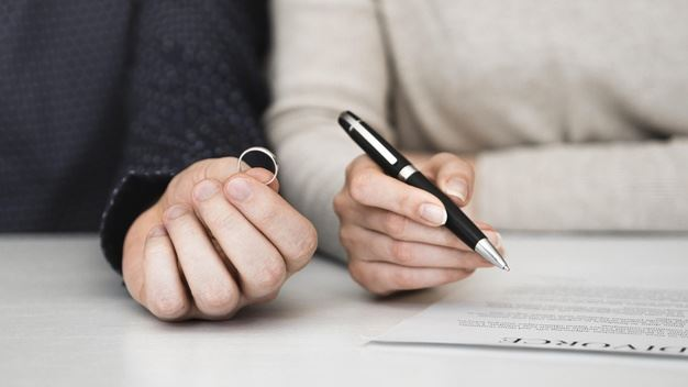 One hand holding a ring, another hand holding a pen over a divorce agreement.